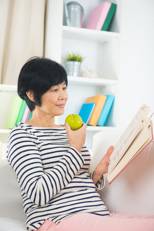 asian matured senior woman reading and eating green apple on a sofa photo