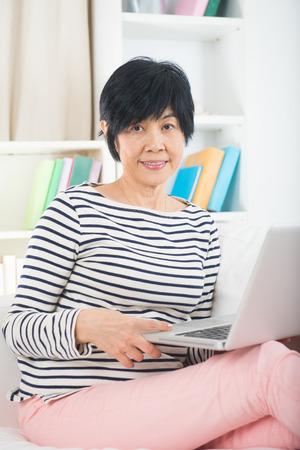 senior asian: asian chinese senior female surfing internet on laptop computer  Stock Photo