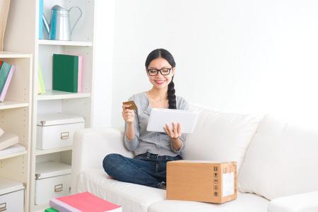asian girl shopping: smiling asian girl online shopping on sofa