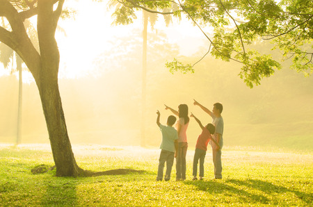 asian trees: family having fun pointing to somewhere during beautiful sunrise