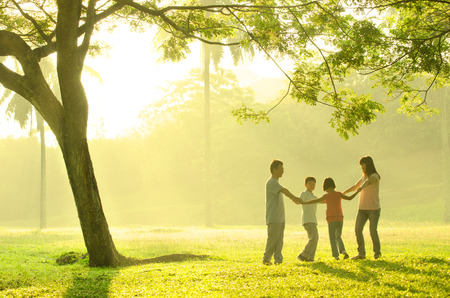 asian trees: asian family having quality time playing together in the park