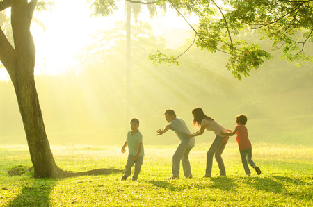 asian family playing with joy in park during a beautiful morning photo