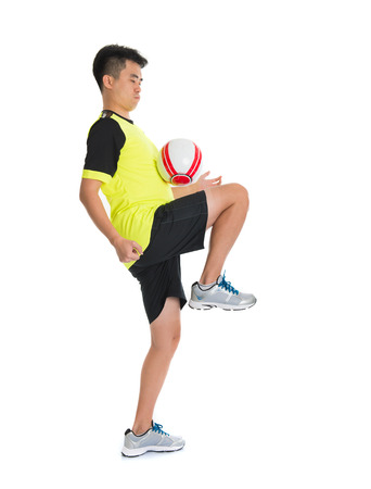 punt: asian man playing soccer isolated on white background