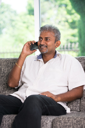 old man sitting: indian mature male on phone conversation with lifestyle background