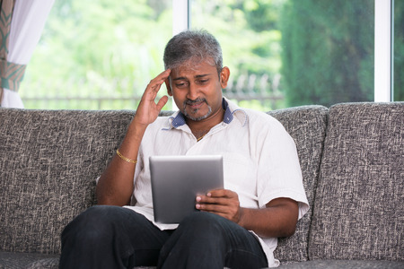 matured indian male in stress worry look with a tablet on a sofa setting photo