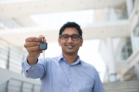 Young Asian Indian estate agent or salesman holding a key, India male business man, real modern office building as background.