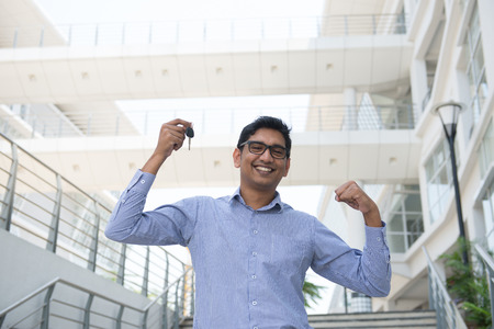 real estate sold: Young Asian Indian estate agent or salesman holding a key, India male business man, real modern office building as background.