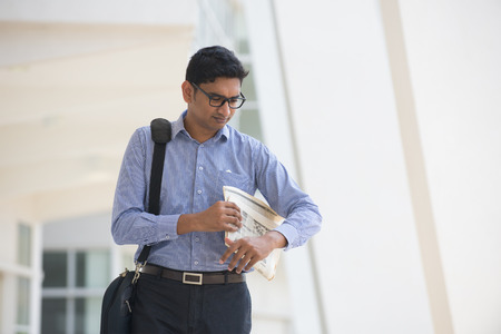 Indian man checking on new office to let, holding newspaper and calling on phone.   photo