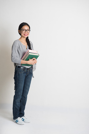asian college girl holding books with copyspace on right