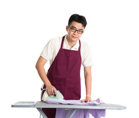 Steam iron: asian chinese male iron shirt and doing laundry work