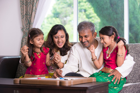 game board:  Indian family playing carrom game at home. Parents and children indoor lifestyle.   Stock Photo
