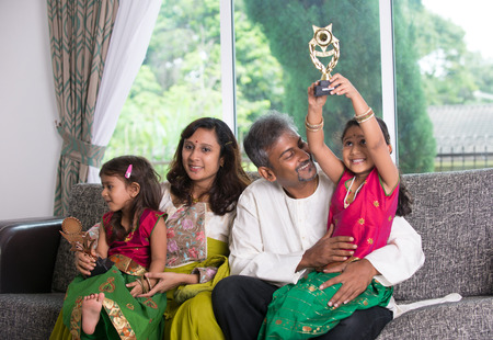 fille indienne: famille indienne célébrant la victoire avec le trophée
