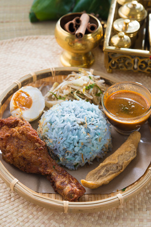 Traditional Malaysian food. Nasi kerabu is a type of nasi ulam, popular Malay rice dish. Blue color of rice resulting from the petals of butterfly-pea flowers. Asian cuisine.   photo