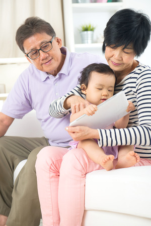 asian senior grand parents teaching grand son with tablet photo
