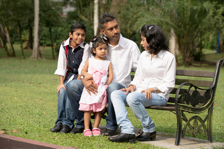 mother on bench: indian family sitting on the bench in the park