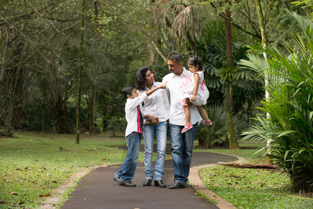 happy indian family walking outdoor in the park