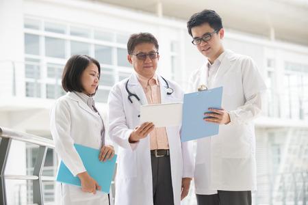 Asiatische medizinische Team von Ärzten, welche im Inneren Krankenhausgebäude