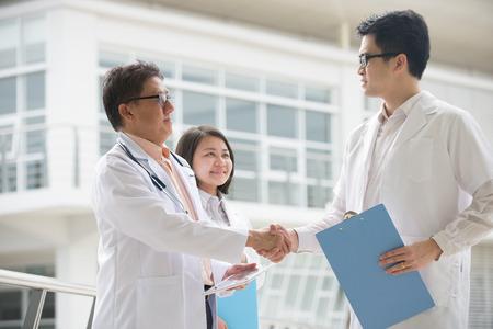 Asian medical team of doctors shaking hands inside hospital building photo