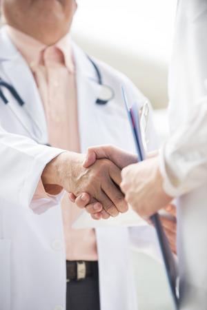 Nahaufnahme Foto asiatische medizinische Team von Ärzten Händeschütteln innen Krankenhausgebäude