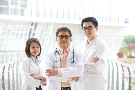 Asian medical team of doctors standing inside hospital building Stock Photo