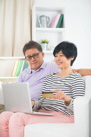 asian senior couple online shopping on the internet with credit card photo