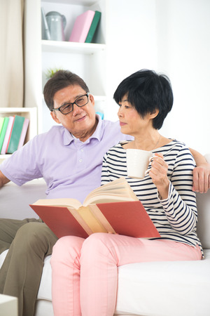 70 year old man: asian senior couple reading book and writing with coffee or tea Stock Photo