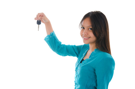 malay girl holding a car key wearing a traditional dress photo