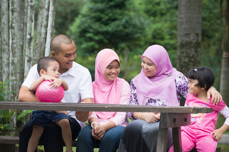 Happy Malay Asian Family enjoying family time together in the park photo