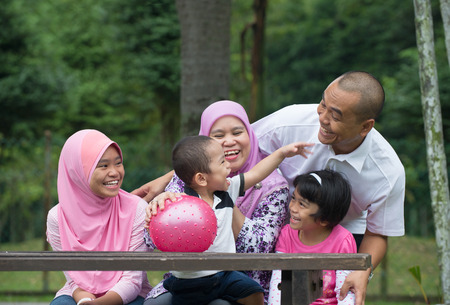 south east asian: Happy Malay Asian Family enjoying family time together in the park Stock Photo