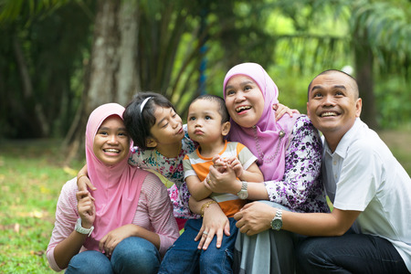 malay muslim family having fun playing in the park Stock Photo