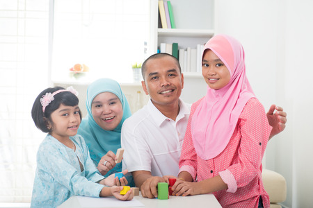 Malay family at home. Muslim girl building a wooden toy house. Southeast Asian parents and child living lifestyle.