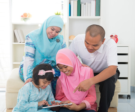 family living: Southeast Asian family surfing internet at home. Muslim family living lifestyle Stock Photo