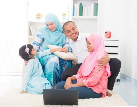 Zuidoost-Aziatische familie surfen internet thuis. Moslim familie wonen lifestyle