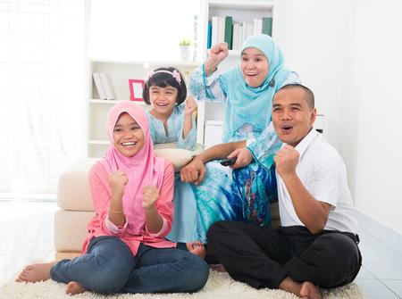 gente viendo television: familia malayo ver televisi�n disfrutar tiempo de calidad Foto de archivo