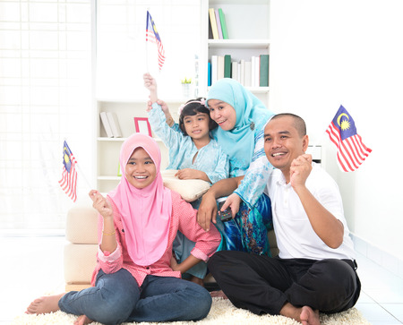 malaysian family celebrating while watching television over a tournament , some are carrying country flags Stock Photo