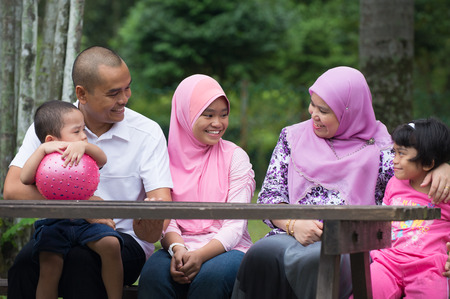 family time: Happy Malay Asian Family enjoying family time together in the park Stock Photo
