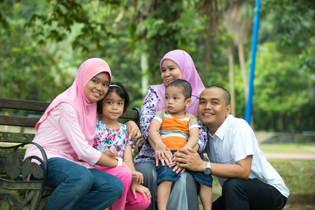 south asians: Happy Malay Asian Family enjoying family time together in the park Stock Photo