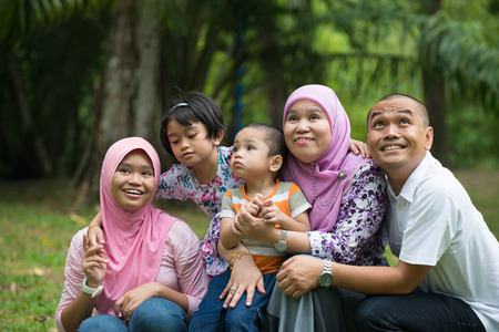 indonesian people: Happy Malay Asian Family enjoying family time together in the park Stock Photo