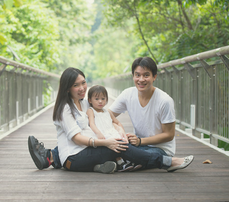 asian family enjoying outdoor park , vintage tone photo