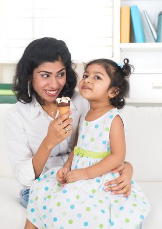 indian mother and child enjoying ice cream indoor photo