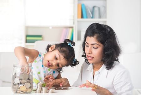 indian Mother and daughter putting coins into bottle, saving plan Stock Photo - 34195268
