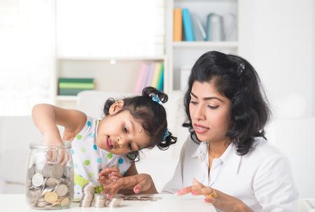 planificacion familiar: Madre e hija indio poner monedas en la botella, el plan de ahorro Foto de archivo