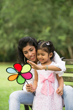 south asian: Happy Indian mother and daughter playing in the park. Lifestyle image. Stock Photo