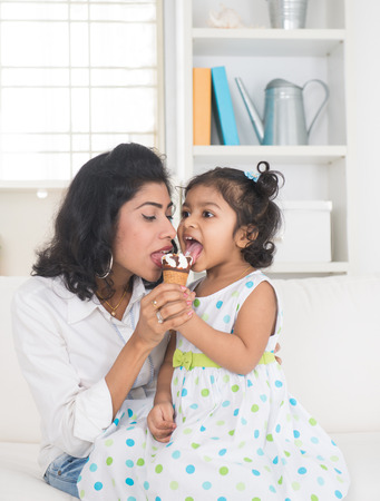 asian foods: indian mother and child enjoying ice cream indoor