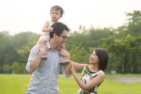 Happy Asian Family enjoying family time together in the park