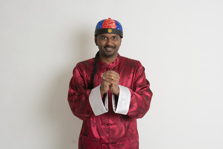 indian male with chinese new year clothes giving greetings photo