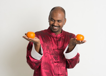 indian male with chinese new year clothes and mandarin oranges photo