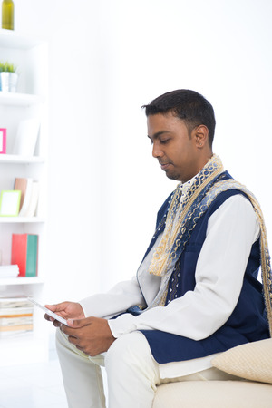 salwar: indian male with tradtional dresss and tablet computer