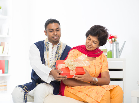 Mature Indian woman receiving a gift from her son photo
