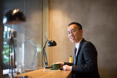 アジア ビジネスの男性がコーヒーを飲んでいます。